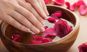 Hände in Schale mit Rosenblättern und Wasser
